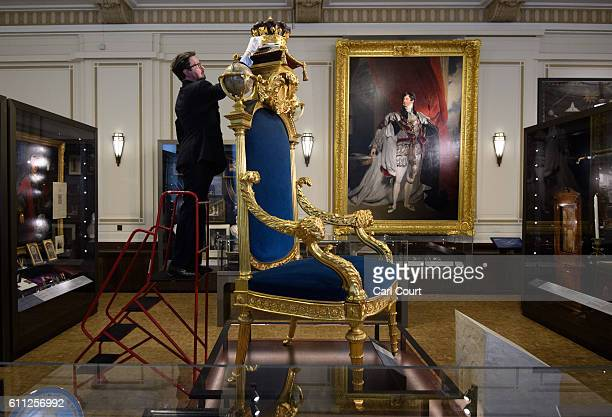 Curator Mark Dennis poses next to the Grand Master's Chair during a press preview for the opening of a gallery titled 'Three Centuries of English...