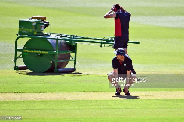Curator Matt Page inspects the wicket in Melbourne on December 25 ahead of the third cricket Test match between Australia and India. / -- IMAGE...