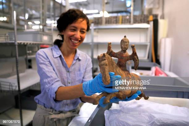 Curator Morag Wilhelm holds an artifact which belonged to Sigmund Freud at the Israel Museum in Jerusalem on July 12 2018 A new exhibition in...