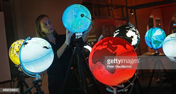 Curator Olga Subiros checks globes visualising world data at the Big Bang Data exhibition at Somerset House on December 2 2015 in London England The...