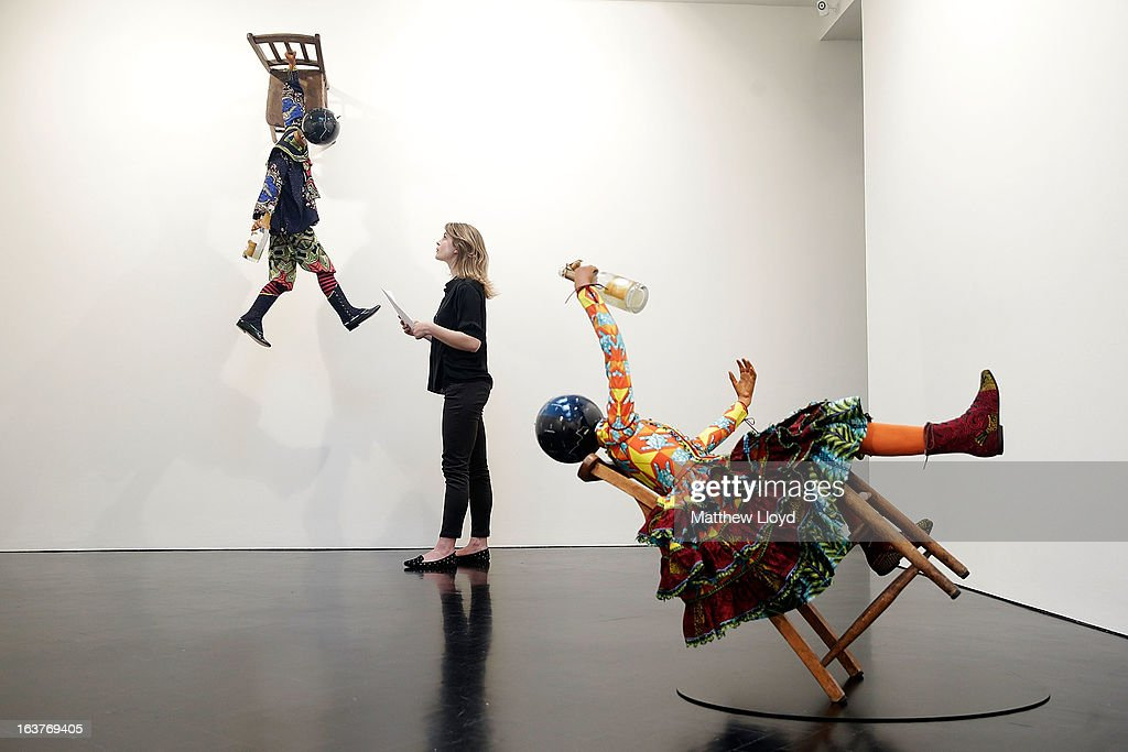 A curator poses alongside sculptures 'Champagne Kid (hanging)' and 'Champagne Kid (leaning)', part of the Pop! exhbition by Yinka Shonibare, MBE at the The Stephen Friedman Gallery on March 15, 2013 in London, England. The exhibition, which explores themes of corruption and excess, runs from 16th March to the 20th April 2013.