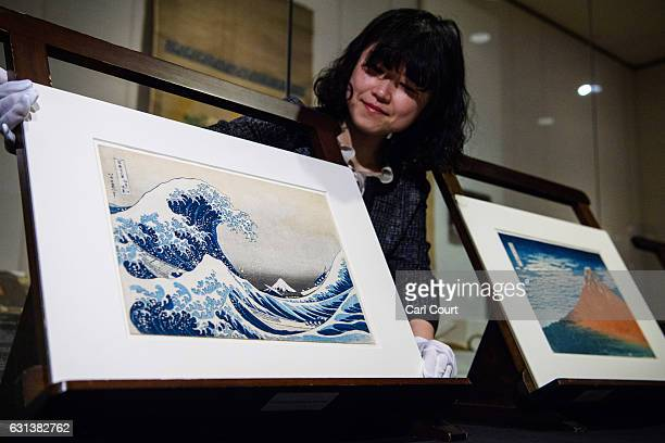 A curator poses for a photograph between a colour wood block print entitled 'The Great Wave off Kanagawa' and another print titled 'Red Fuji' during...