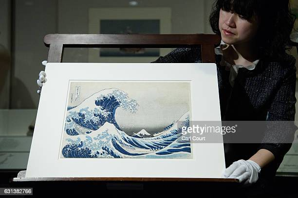 A curator poses for a photograph with a colour wood block print entitled 'The Great Wave off Kanagawa' during a press preview for an exhibition by...