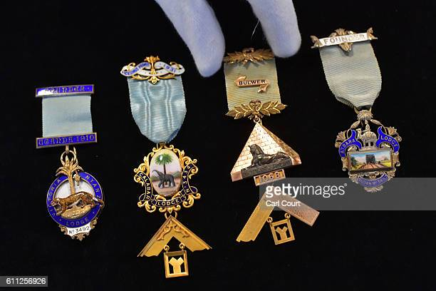 A curator poses with Masonic badges known as Jewels during a press preview for the opening of a gallery titled 'Three Centuries of English...