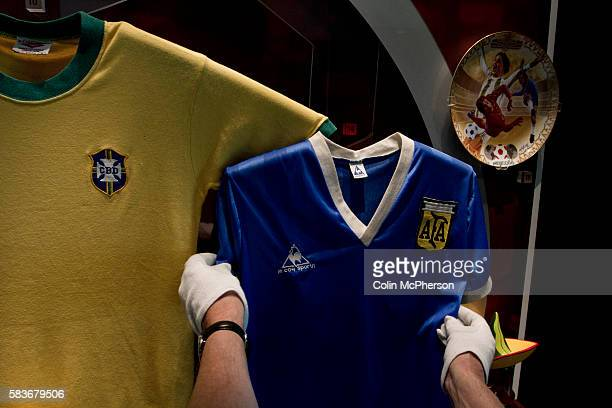 A curator putting the final touches to one of the displays featuring Maradona's 'Hand of God' shirt at the National Football Museum in Manchester...