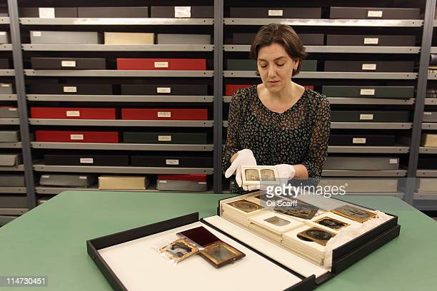 Curator Sarah McDonald holds Daguerreotype images from the 1800s in the Vintage Room of historic photographs in the Hulton Archive on May 12 2011 in...