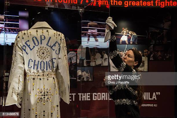 Curator Shannon Pratt 37 polishes a case containing a 'People's Choice' robe presented to Muhammad Ali by Elvis Presley at the preview of the 'I Am...