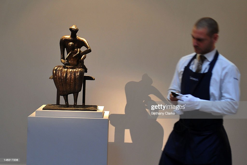 A curator stands next to 'Mother & Child with apple' by Henry Moore (1956) which is on display at Sotheby's on June 14, 2012 in London, England. This piece is part of the Impressionist & Modern and Contemporary Art sale at Sotheby's which will be held on June 19, 2012 and June 20, 2012.