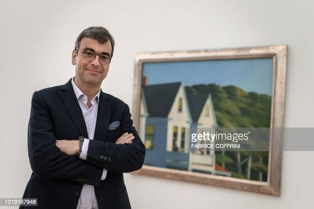 Curator Ulf Kuester poses next to a painting by US painter Edward Hopper entitled Second Story Sunlight after the reopening of the exhibitions Edward...