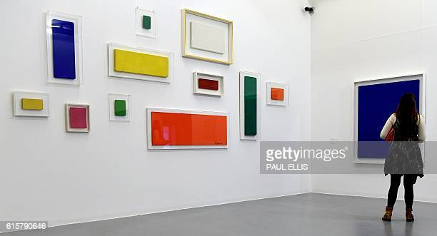 Curator walks past untitled works by French artist Yves Klein on display as part of the launch of the winter season at the Tate gallery in Liverpool,...