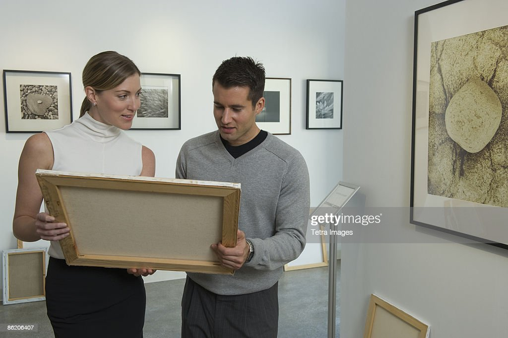 Curators examining painting in art gallery : Stock Photo