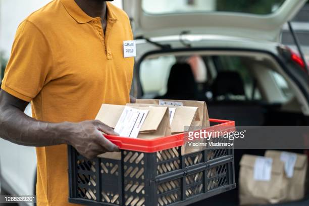 curbside pickup service staff holding a basket with food delivery - curbside pickup stock pictures, royalty-free photos & images