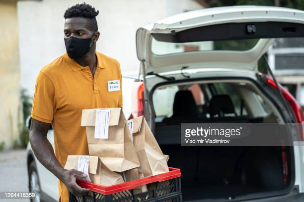 curbside pickup with a protective face mask holding a basket with food delivery - curbside pickup stock pictures, royalty-free photos & images