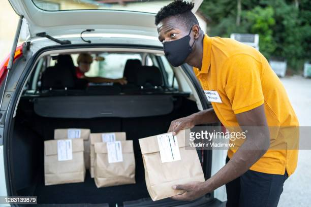 curbside service staff loading shopping bags for customer while staying in car - curbside pickup stock pictures, royalty-free photos & images