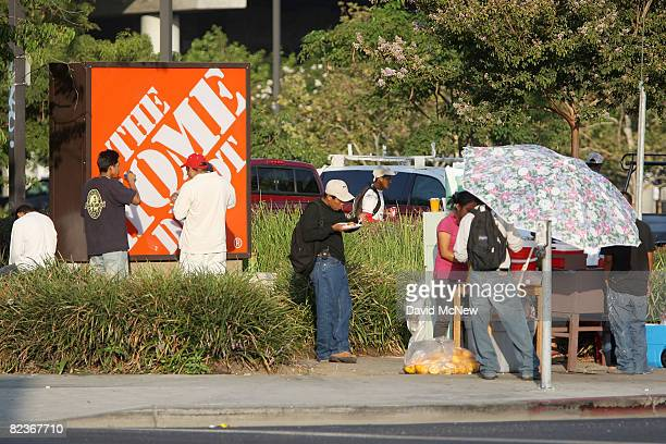 A curbside vender sells food to day laborers waiting near a Home Depot home improvement store in hope of finding work for the day on August 15 2008...