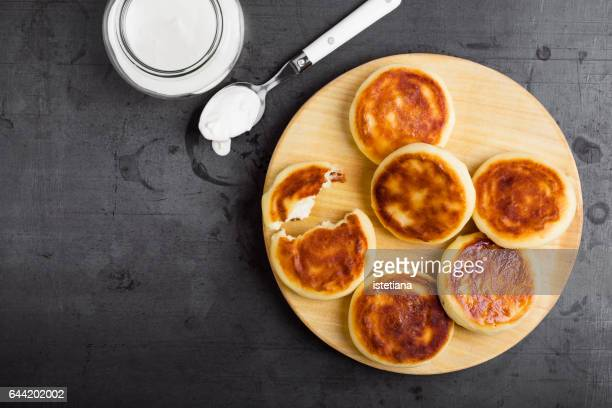 Curd cheese pancakes on rustic board served with sour cream