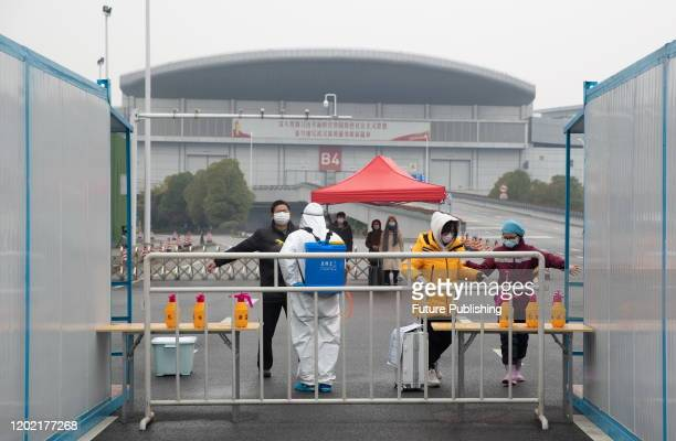 Cured Chinese patients who were infected with the new coronavirus are disinfected before leaving a Fangcang mobile cabin hospital in Wuhan City,...