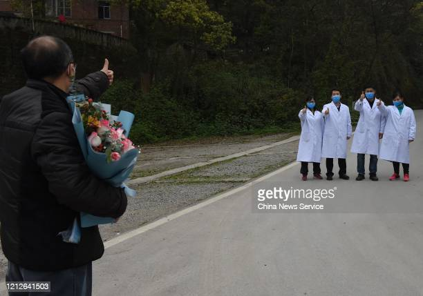A cured COVID19 patient thumbs up to medical workers as he is discharged from Chongqing Public Health Center on March 15 2020 in Chongqing China The...