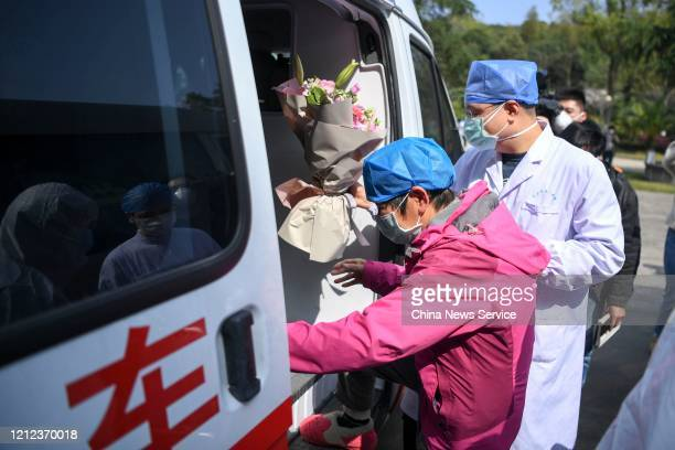 Cured patient of the novel coronavirus infection boards a vehicle as she is discharged from the hospital on March 14, 2020 in Changsha, Hunan...
