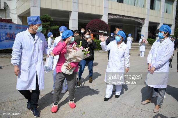 Cured patient of the novel coronavirus infection waves to medical workers as she is discharged from the hospital on March 14, 2020 in Changsha, Hunan...