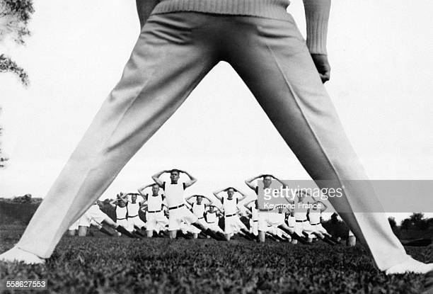 Curieuse photographie montrant au premier plan les jambes d'un segentmajor qui dirige l'entraînement de l'école militaire de culture physique à...