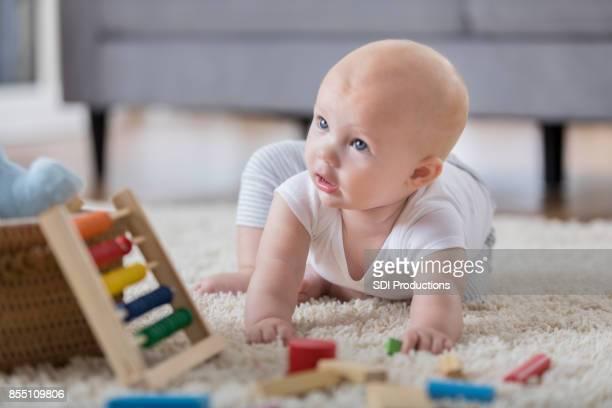 Nieuwsgierig baby kruipt op de verdieping