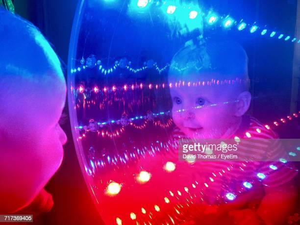 Curious Baby With Reflection On Illuminated Tunnel