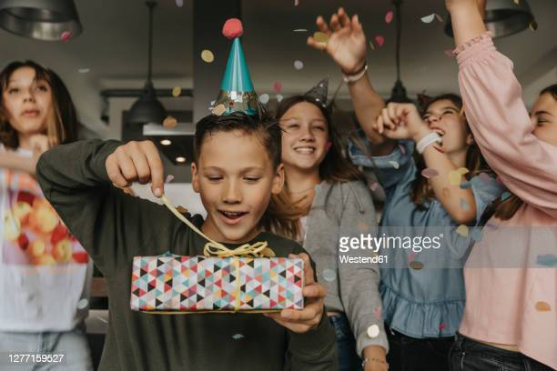 curious birthday boy opening gift while friends dancing in background - birthday stock pictures, royalty-free photos & images