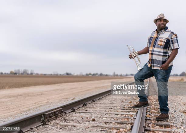 Curious Black man standing on train track holding trumpet