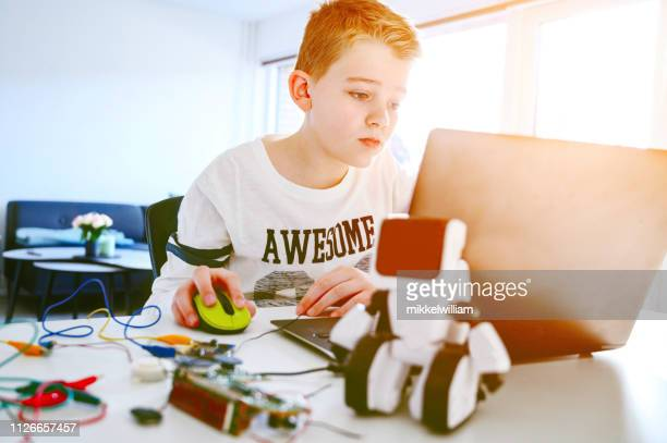 Curious boy creates new inventions with the help of a laptop and electronics