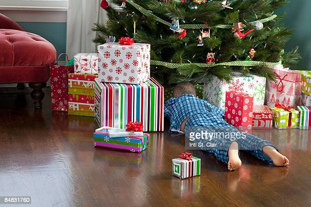 Curious boy digging through presents under tree