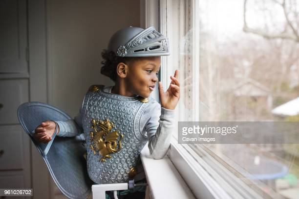 curious boy dressed up in armor costume looking out through window at home - protective workwear stock pictures, royalty-free photos & images