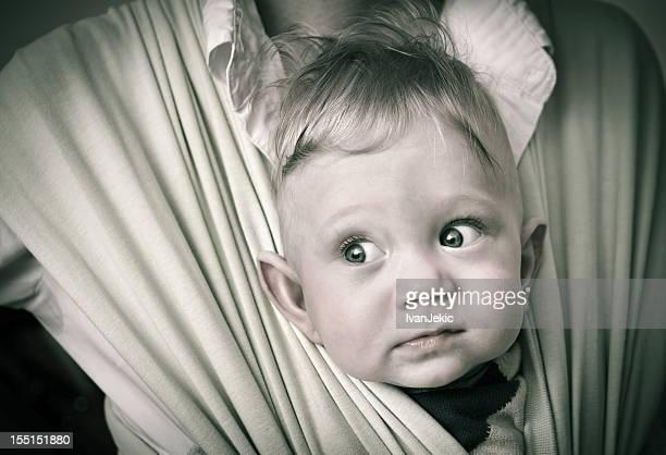 Curieux petit garçon dans un transat pour bébé