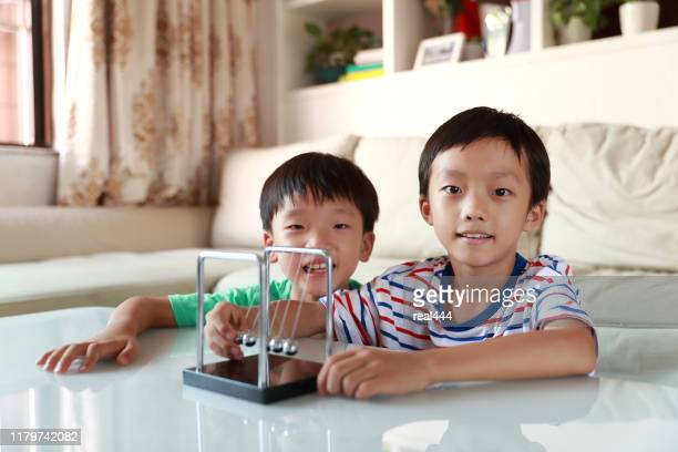 curious boy playing with newtons cradle - silver blouse stock pictures, royalty-free photos & images