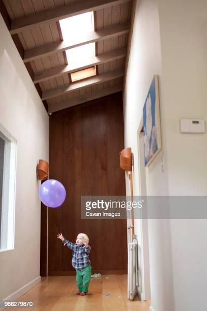 curious boy trying to catch balloon at home - catching stock pictures, royalty-free photos & images