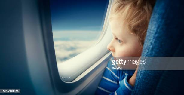 Curious boy watching sky from airplane window