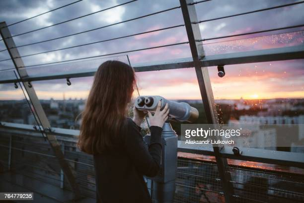 Curious Caucasian admiring scenic view with binoculars