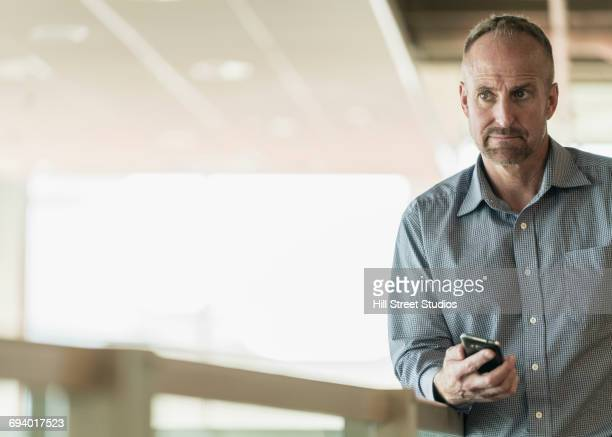 curious caucasian businessman holding cell phone - photography stock pictures, royalty-free photos & images
