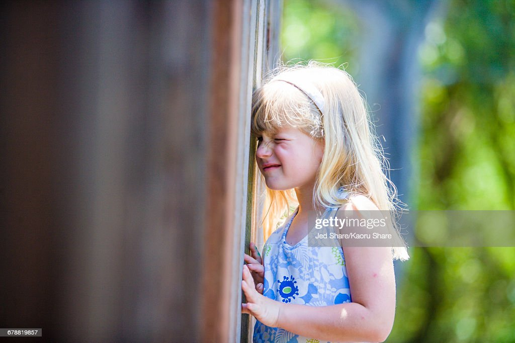 Curious Caucasian girl peeking through wooden fence : Stock Photo