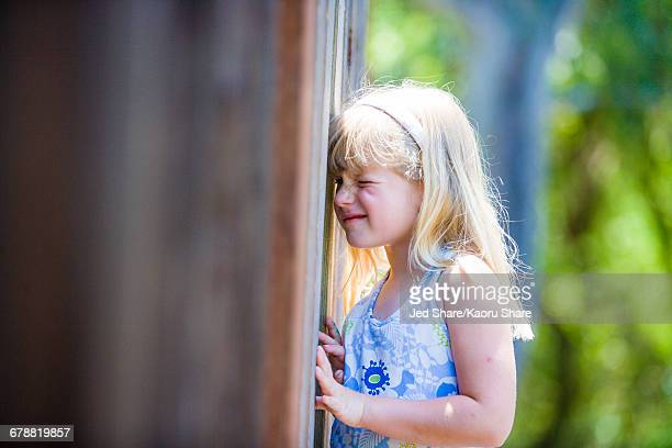 Curious Caucasian girl peeking through wooden fence