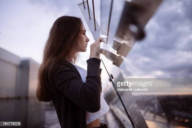 curious caucasian woman peering over glass wall at scenic view - curiosity stock-fotos und bilder