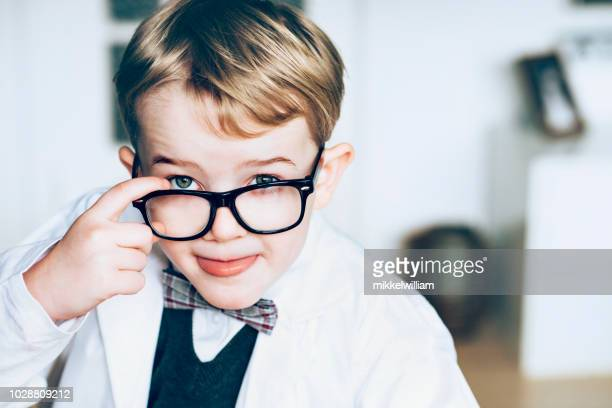 Curious child dressed as a scientist looks at something interesting or delicious