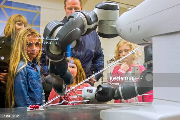 Curious children looking at demonstration with industrial robot arms at exposition about robotics and artificial intelligence AI