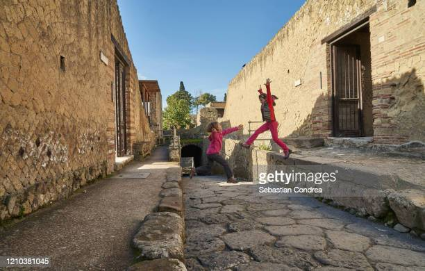 curious children, who jummping into the archaeological park of ancient ercolano (herculaneum) city ruins. naples, campania, italy - crash site stock pictures, royalty-free photos & images
