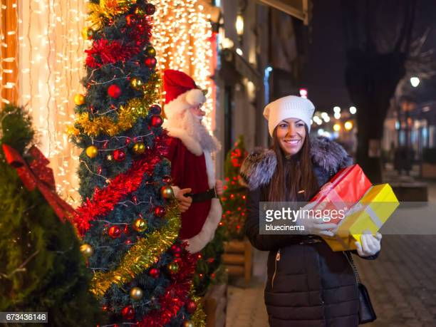 Curious Christmas Girl with Presents in street