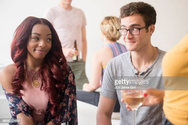curious couple flirting at party - verlegen stockfoto's en -beelden
