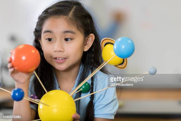 curious female student examines solar system model - solar system stock pictures, royalty-free photos & images
