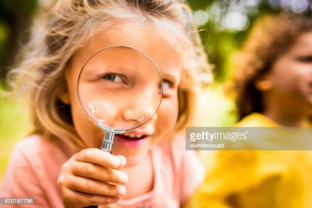 Curious girl holding a magnifying glass playfully