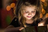 Curious girl peeks inside a Christmas present