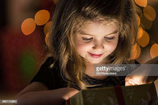 Curious girl peeks inside a Christmas present